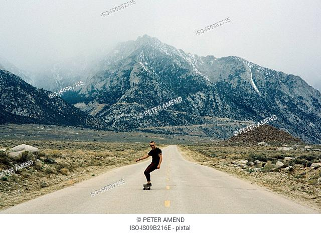 Man skateboarding on road by mountains, Lone Pine, California, USA