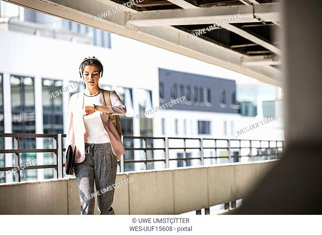 Young businesswoman walking in parking garage, checking time