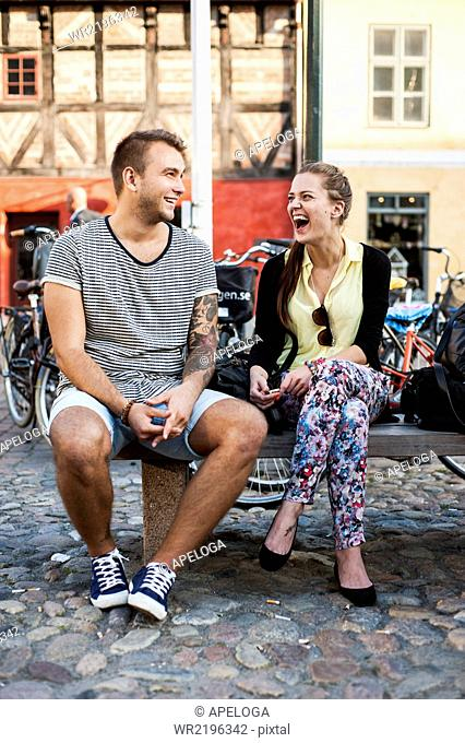 Full length of young friends laughing while sitting on bench in city