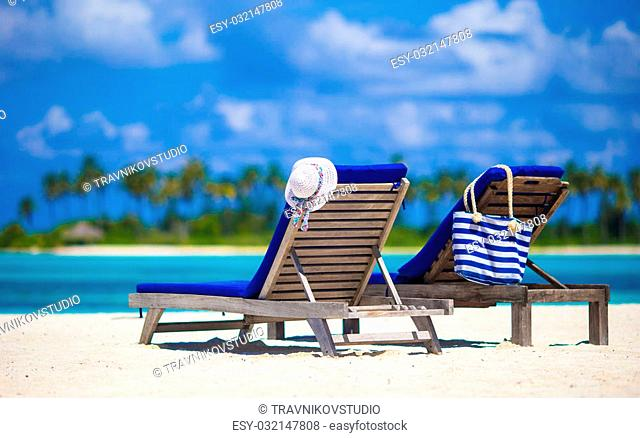 Lounge chairs with stripe bag and hat on tropical beach at Maldives