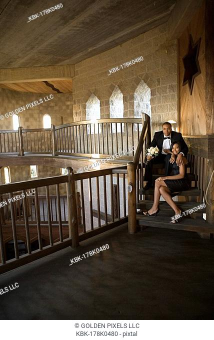 Young couple in formal attire sitting on stairs inside medieval castle