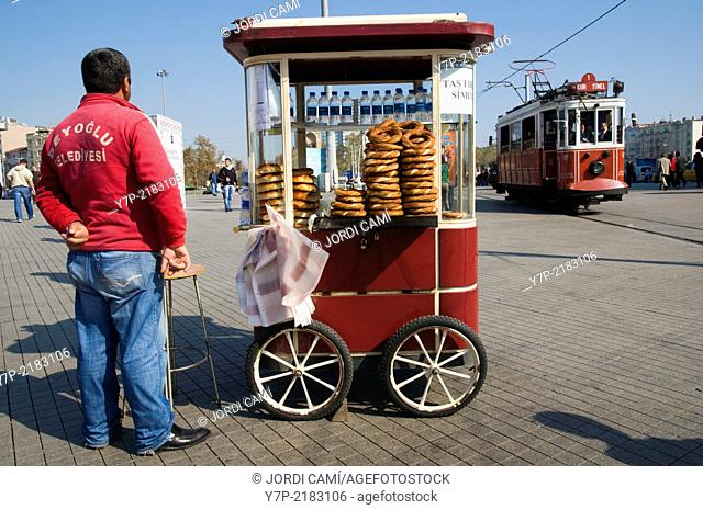 Simit sesame bread rings for sale and the old tram in Taksim Square , Istanbul, Turkey, Middle East