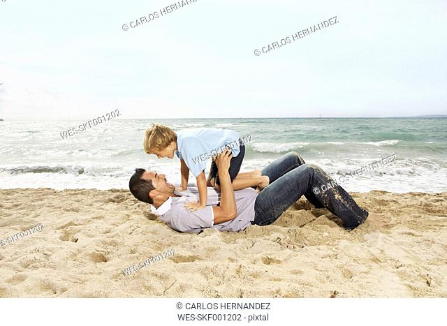 Spain, Father and son having fun on beach at Palma de Mallorca, smiling