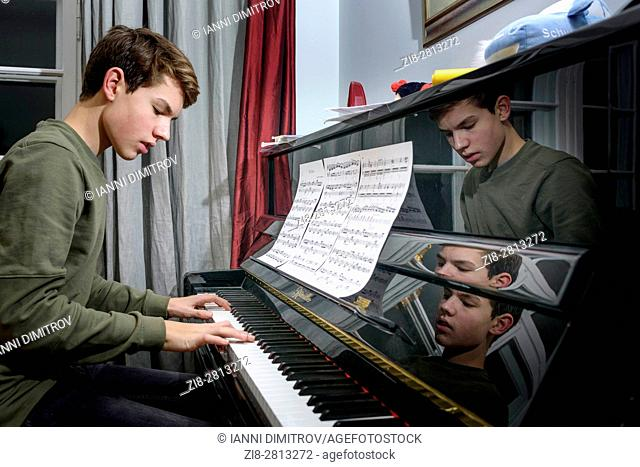Teenage boy practicing piano at home
