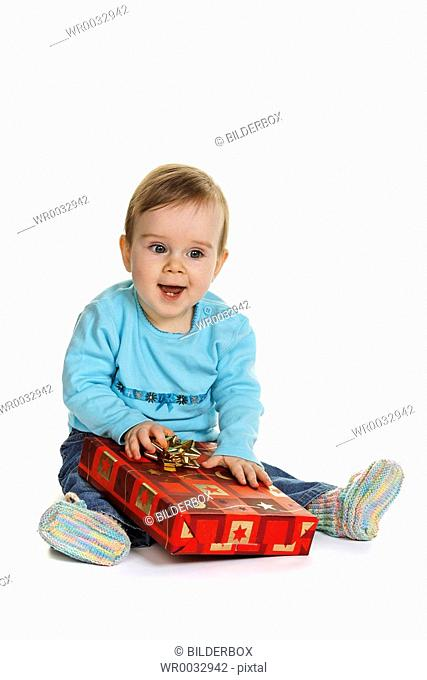 Small child baby with a gift package for Christmas