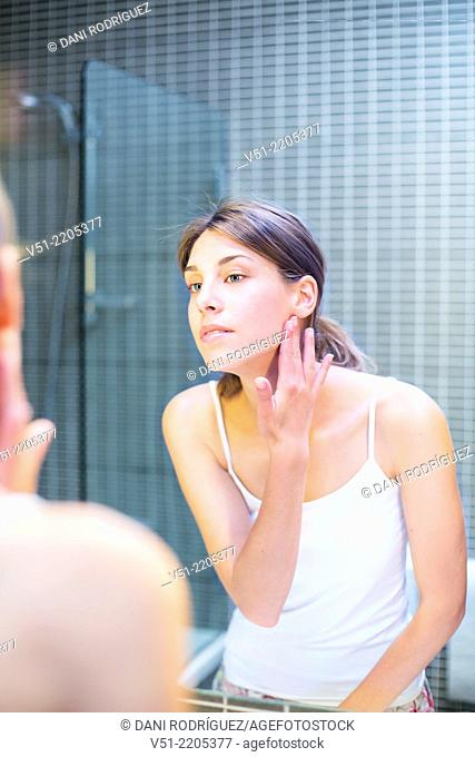Young woman looking at herself in the mirror in the bathroom