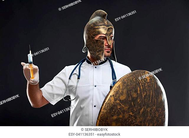Shot of a brave medical worker doctor wearing a helmet holding a shield and a syringe looking around ready to fight illnesses and diseases posing on dark...