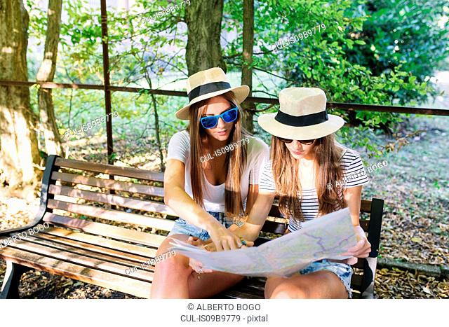 Two young female friends sitting on bench looking at map in park