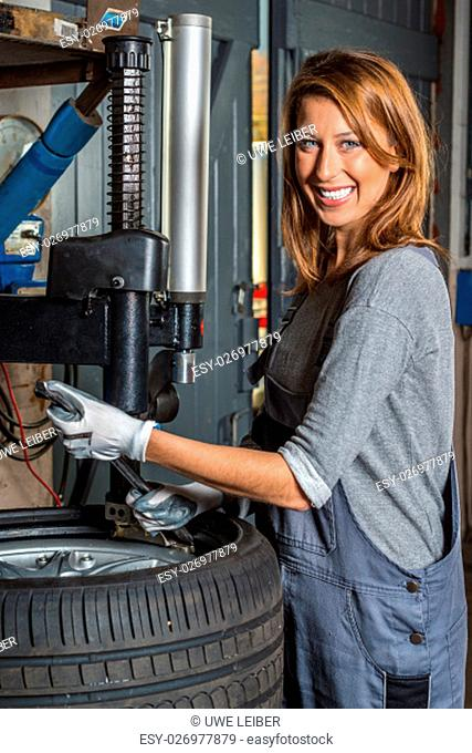 Young Female car mechanic changing car tyre in auto repair shop with a machine and a big wrench
