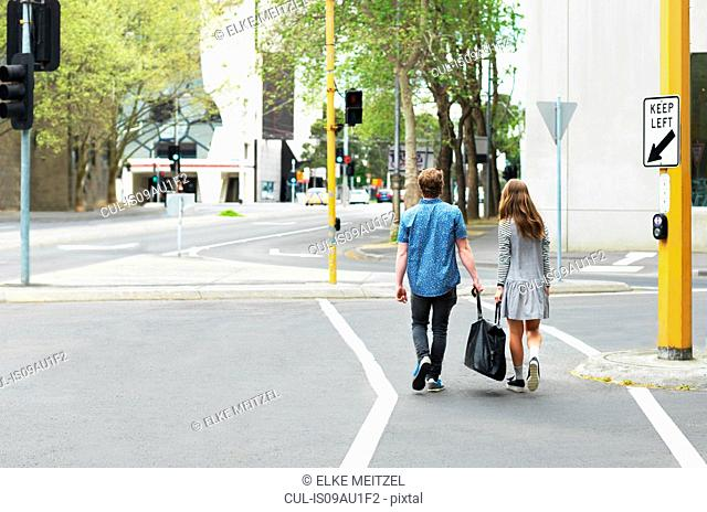 Young couple carrying bag together on street, Melbourne, Victoria, Australia