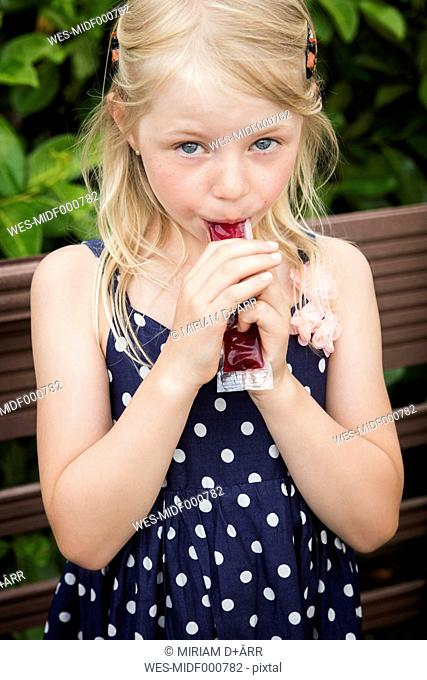 Blond little girl eating water ice