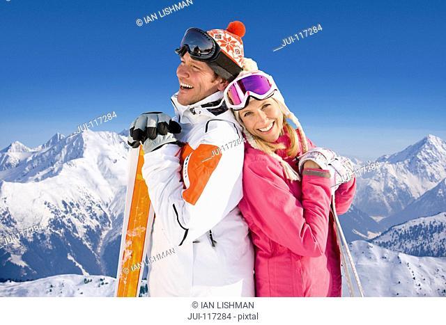 Couple Enjoying Winter Ski Holiday In Mountains