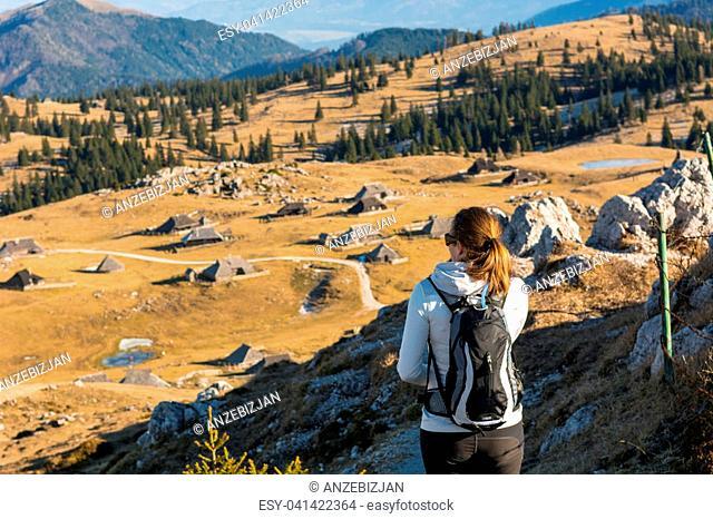 Woman enjoying highland settlement view. Velika planina, Slovenia