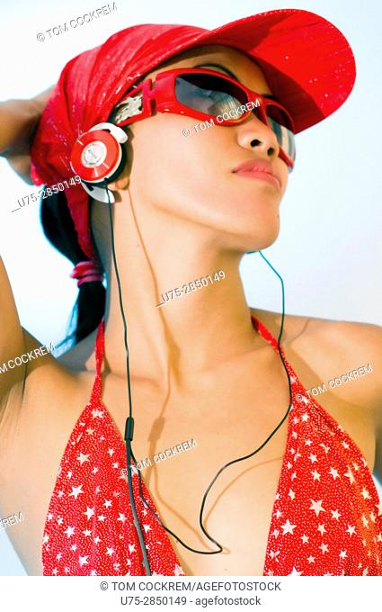 Young Asian woman with earphones in studio setting