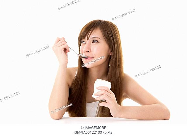 Young woman looking away with spoon in mouth