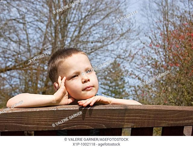This little boy has an expression as tho dreaming for summer with the bare branches of early spring in the background Background is intentionally blurred for...