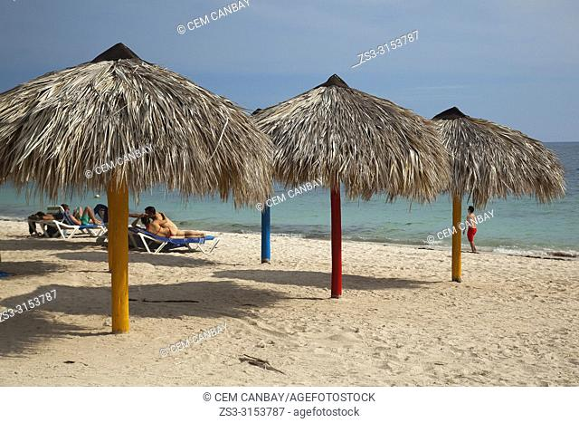 Tourists sunbathing under the thatched umbrellas at the sandy Ancon beach-Playa Ancon, Trinidad, Sancti Spiritus Province, Cuba, Central America