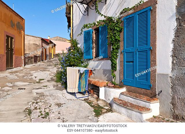 Dryer clothes in front of the Italian village house with a blue door, blue window and blue flowers