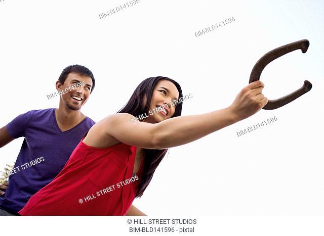 Couple playing horseshoe together outdoors