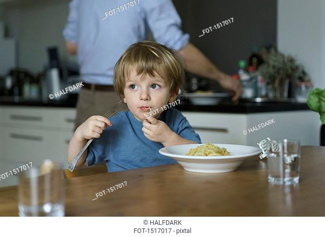 Boy eating noodles while father working in kitchen at home