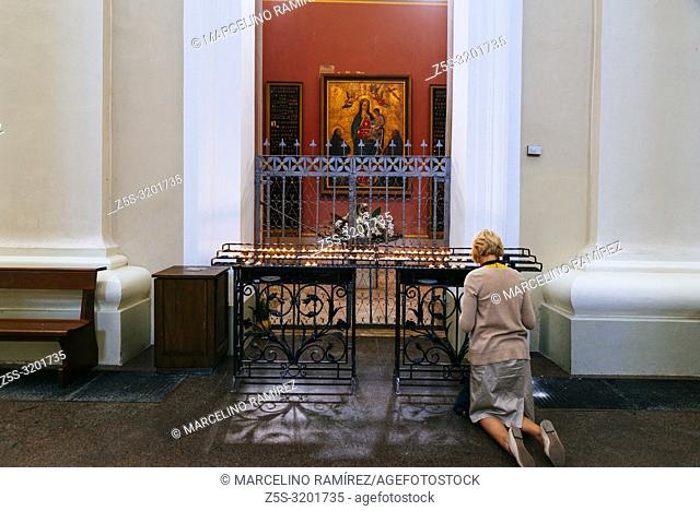 Woman kneeling in front of the virgin image and votive offerings. Cathedral Basilica of St Stanislaus and St Ladislaus of Vilnius is the main Roman Catholic...