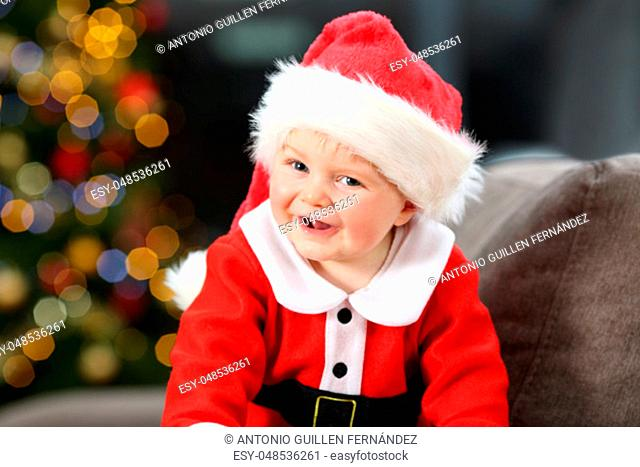 Cute baby wearing santa disguise looking at you