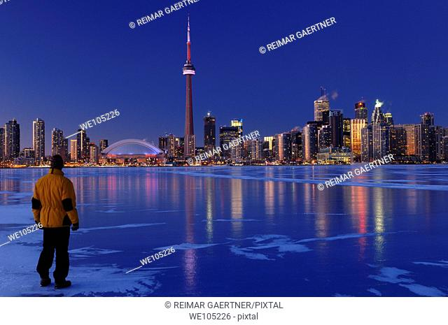 Man standing on frozen Lake Ontario watching Toronto city skyline light up at dusk