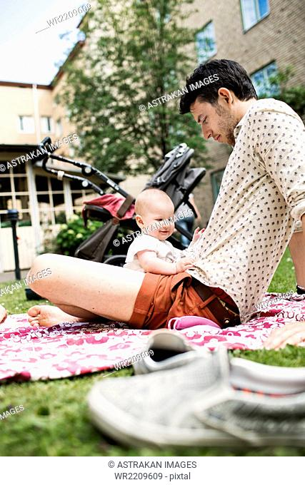 Baby girl with father sitting at yard