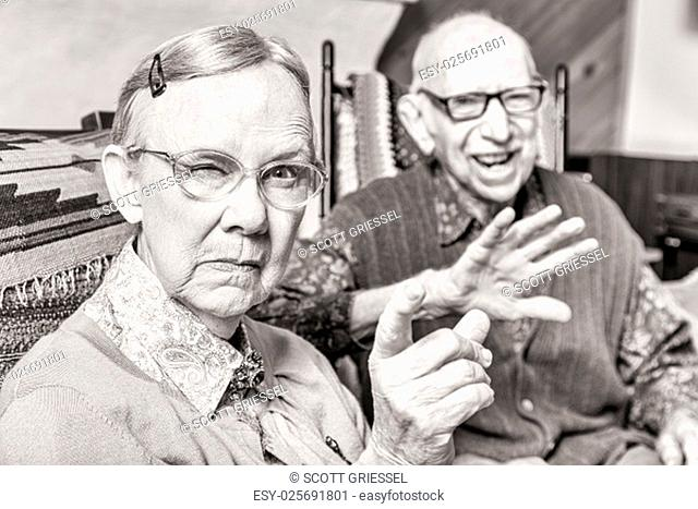 Toned image of angry old couple sitting in living room woman pointing