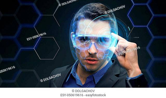 future technology, business and people concept - businessman in 3d glasses with virtual hologram over dark background