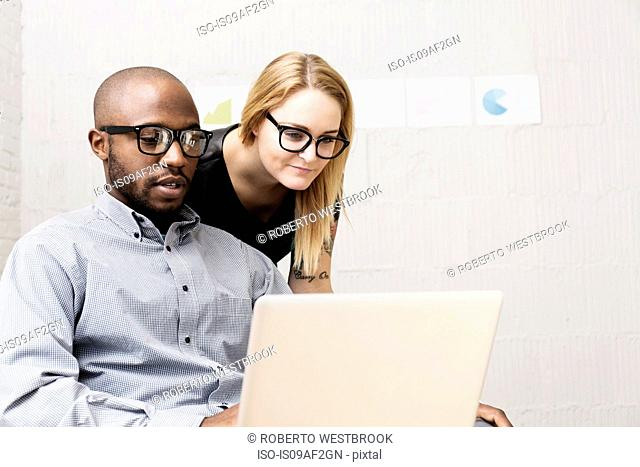 Young business partners looking at computer in design office