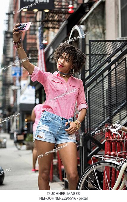 Young stylish woman taking selfie on street