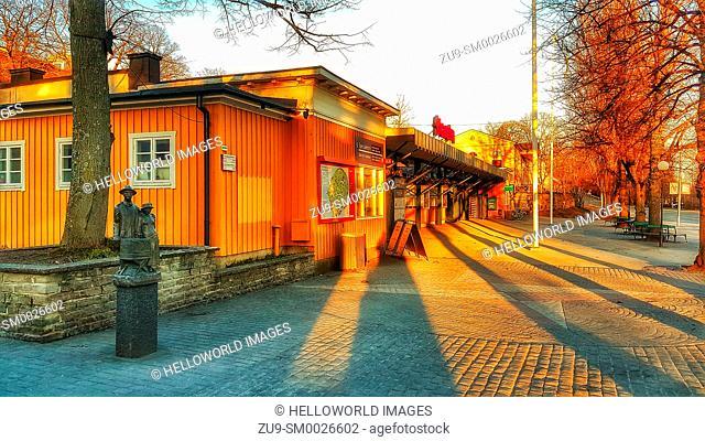 Golden sunset light on the entrance to Skansen open-air living museum, Djurgarden, Stockholm, Sweden, Scandinavia. The sculpture shows a singing couple