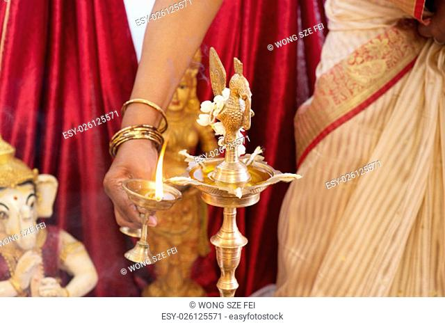 Woman lighting up the metal diya. Traditional Indian Hindus religious ceremony. Focus on the oil lamp. India special rituals events