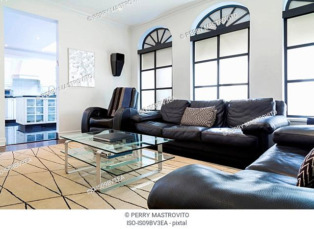 Dark brown leather love seat, sofa and reclining armchair, glass and aluminium coffee table in family room, beige rug and Palladian windows