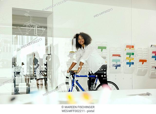 Smiling young woman with bicycle in office