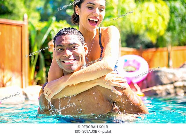 Mid adult man carrying young woman on back in swimming pool looking at camera smiling
