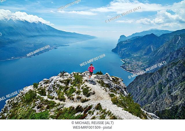 Italy, Trentino, woman running on mountain peak at Lake Garda