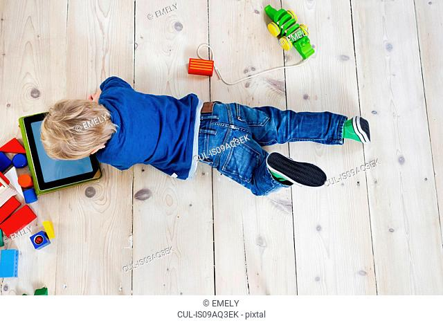 Boy playing with digital tablet on wooden floor