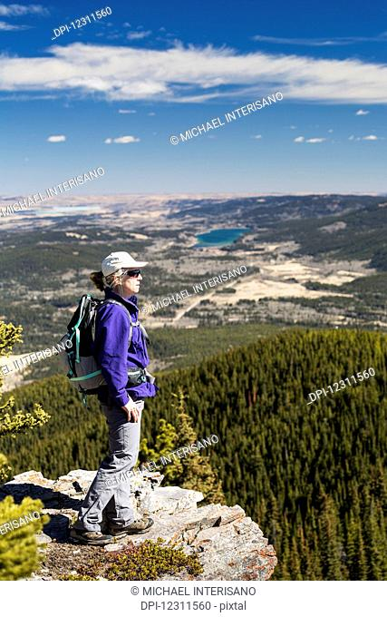Female hiker on rocky cliff edge overlooking valley below with rolling hills, lake, blue sky and clouds, Kananaskis Country; Alberta, Canada