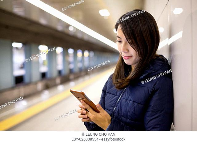 Woman using mobile phone in metro station