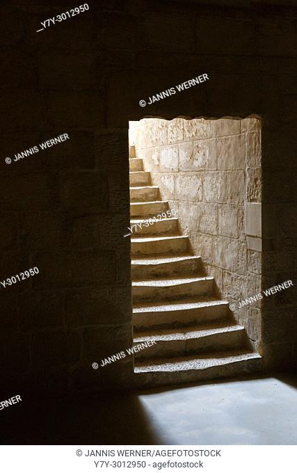 Brightly lit stairs leading from dark interior at Fort St. Elmo, Valletta, Malta