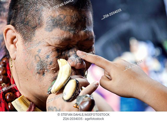 Child Finger touching Nose of tattooed Man on the Chatuchak Market in Bangkok