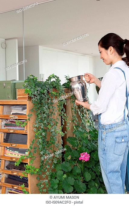 Young woman watering house plants
