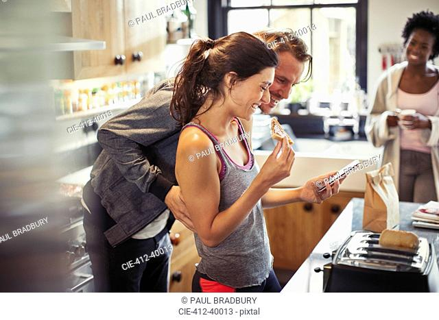 Smiling couple texting with smart phone, eating toast in kitchen