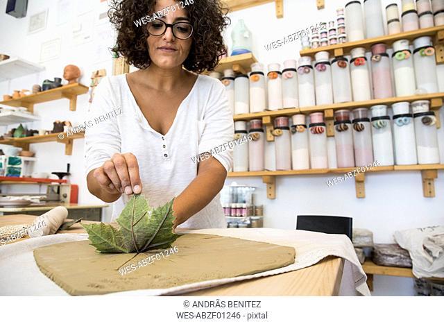 Woman using a leaf to print a draw in terracota in a ceramics workshop