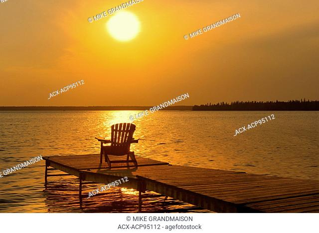 Muskoka chair on dock at Clear Lake, Riding Mountain National Park, Manitoba, Canada