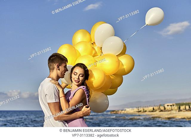 couple embracing, balloons, seaside