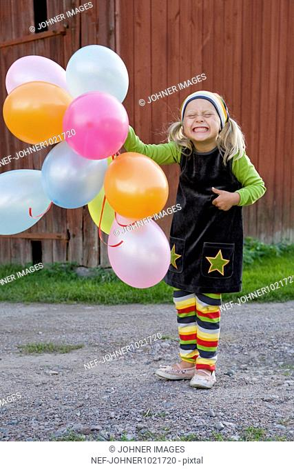 Girl holding balloons with cheeky smile