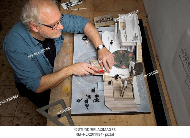 High angle view of man making set of stage theater in workshop